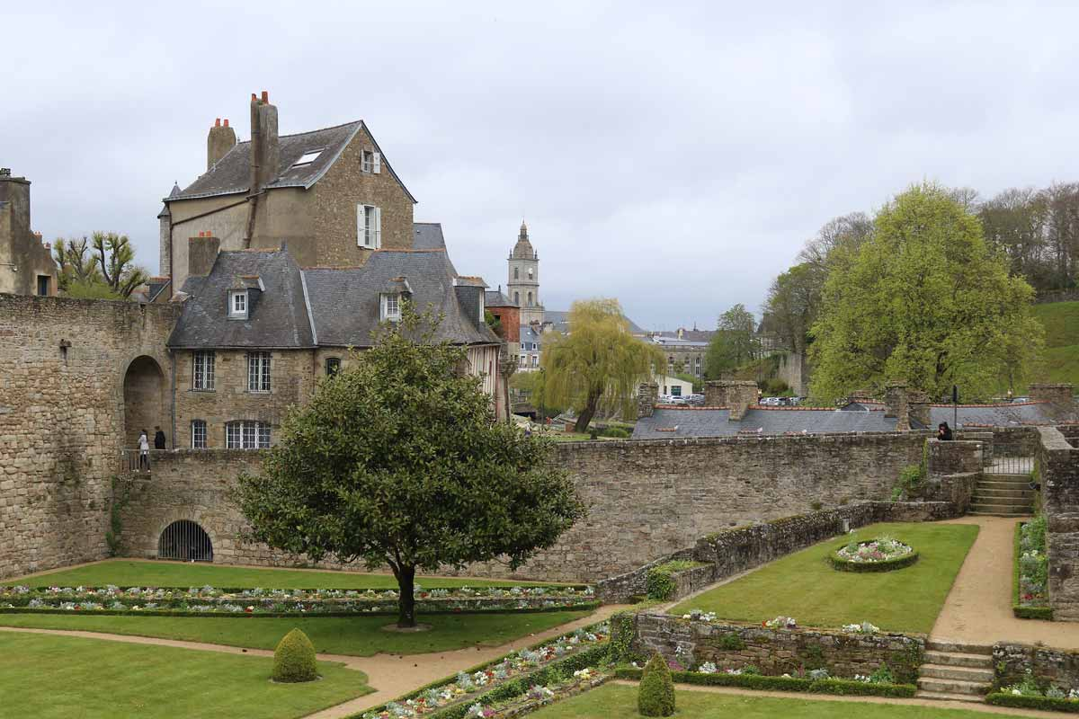 View of a Breton chateau and its gardens on a cloudy day in Brittany.