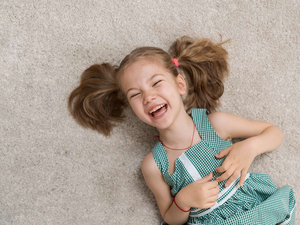 Young girl lying on the floor on her back laughing at deer puns.
