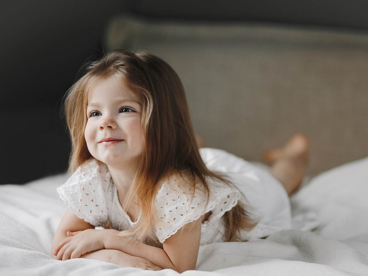 Little girl lying on the bed smiling as she listens to deer puns.