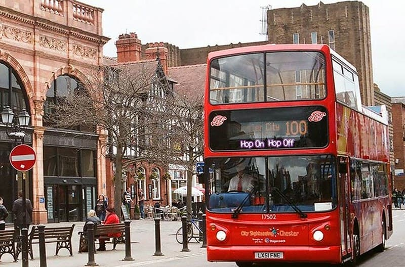 A red City Sightseeing bus in front of old buildings in Chester.