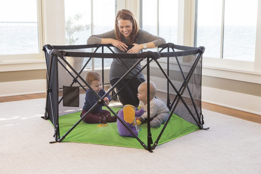 Two babies play under supervision in the Summer Infant Pop 'N Play Playpen.