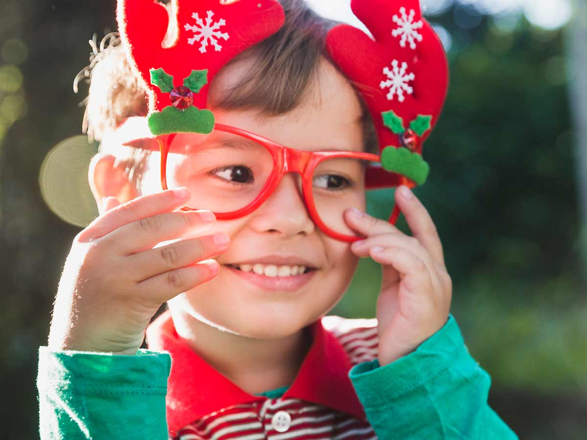 Young boy standing outside smiling, wearing red Christmas glasses with antlers ears on them.