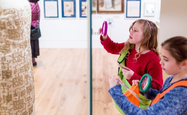 Two kids examining a museum display with a magnifying glass.