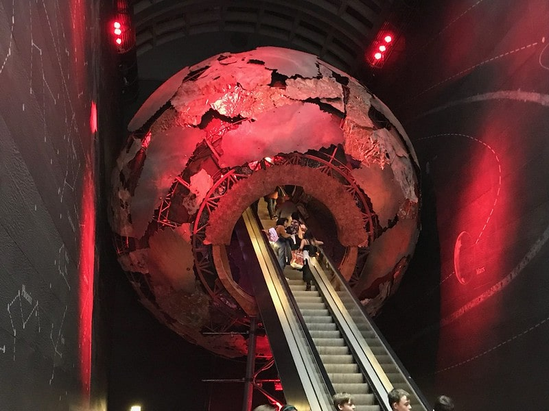 Escalator going up through a model of the planet.
