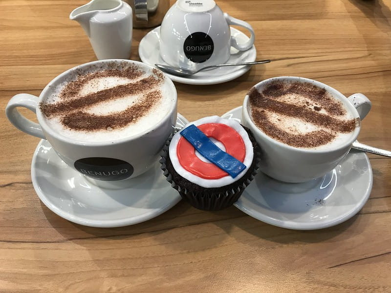 Underground roundel-themed refreshments: a cupcake and two mugs of coffee.