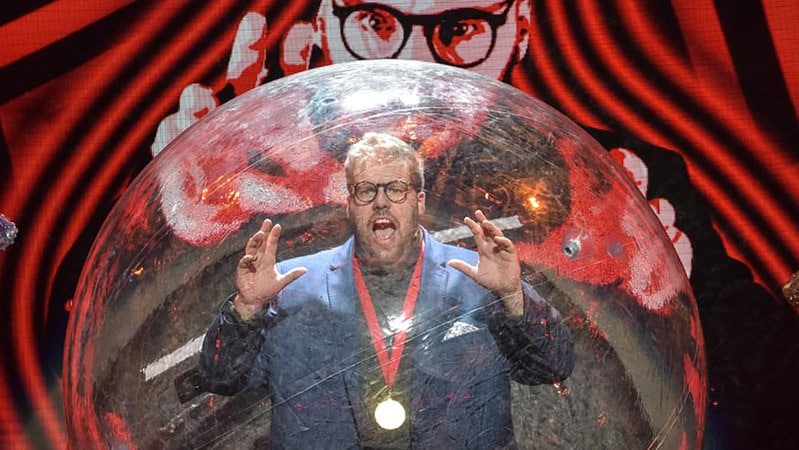 An actors performing inside a glass bubble on stage at Magic Goes Wrong.