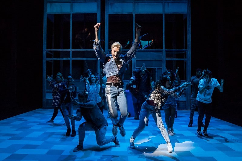 The main character, Jamie New, of Everybody's Talking About Jamie jumping in the air with the cast dancing behind him
