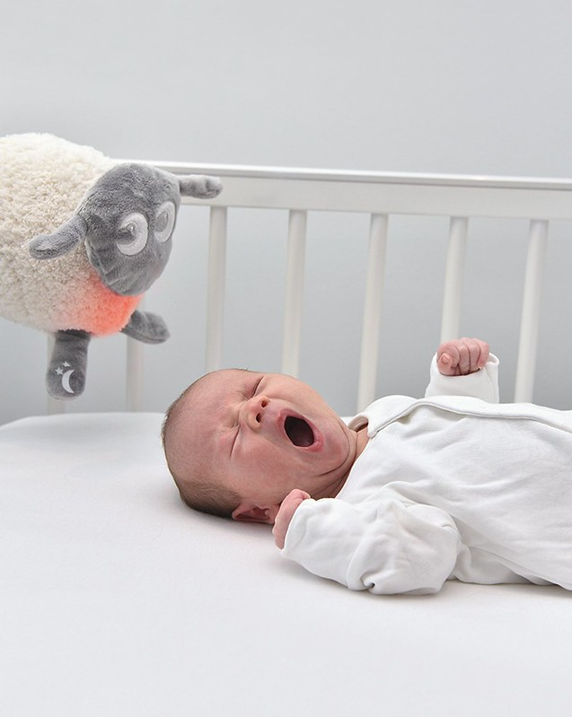 Baby sleeping in a cot with Ewan Dream Sheep Deluxe.