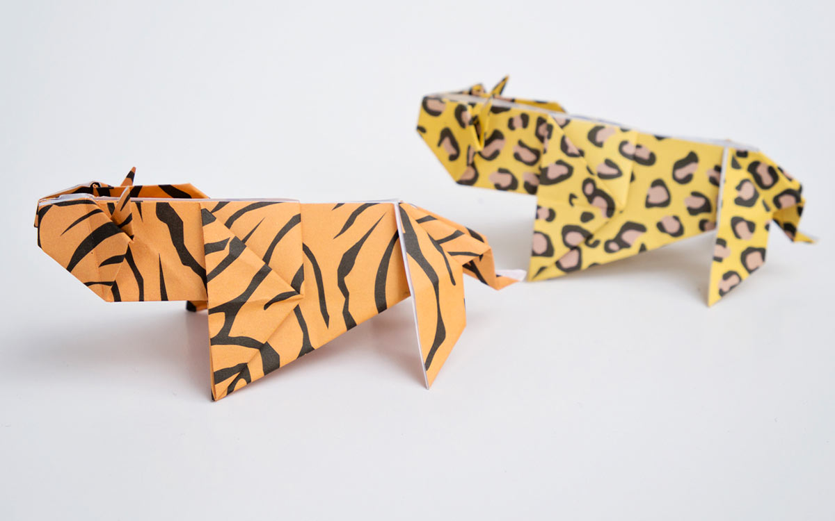 Two origami wild cats: one tiger made from orange paper with stripes, and one cheetah.