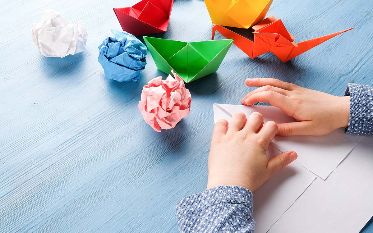 Close up of hands folding paper making origami animals.