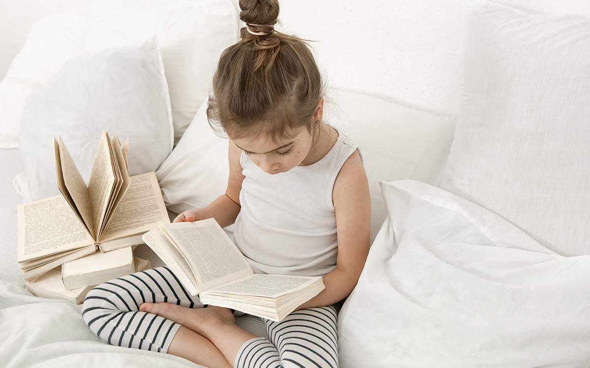 A KS2 girl sat on the sofa reading a book to help her learn about the possessive apostrophe.