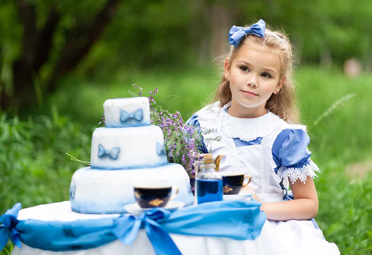 Little girl dressed as Alice in Wonderland sat at a table outside having a tea party with a tiered blue and white cake.