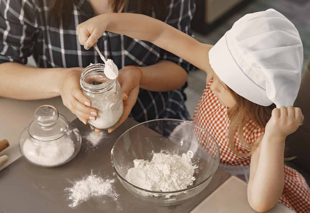 Little girl in a chef's hat spooning flour into a large mixing bowl to make the batter of a frog cake.