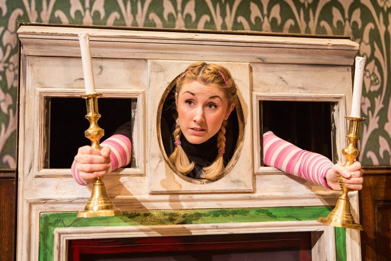 An actress in The Play That Goes Wrong with her head through a hole holding two candlesticks.