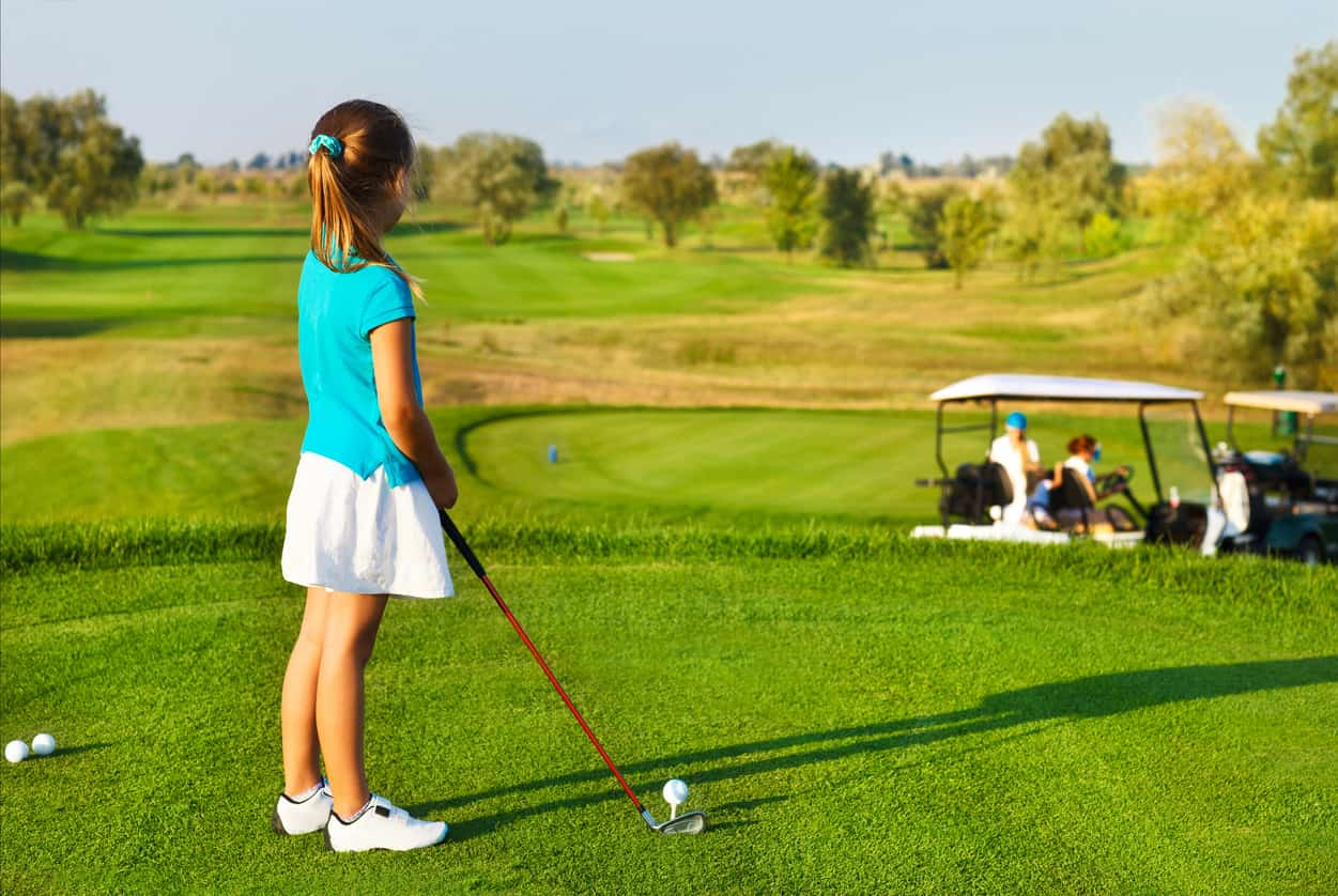 A young girl holding a kids' golf club stands with her back to the camera looking out over the golf course.