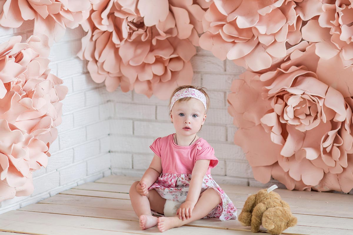 Little girl wearing pink sat on the floor surrounded by pink flower decorations.