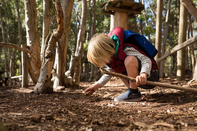 Little child with a backpack on their back crouching down inspecting a rock in the forest.