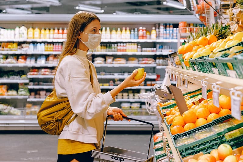 Woman wearing a white face mask in the supermarket buying a lemon.
