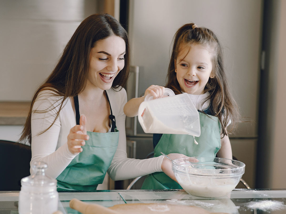 Mum and daughter in the kitchen adding the ingredients to the Peppa Pig cake batter.