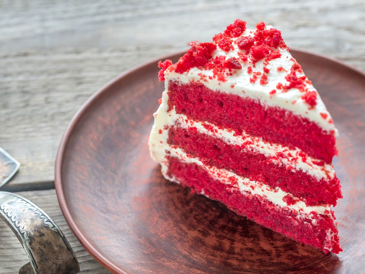Slice of red velvet cake with white frosting and cake crumb on top.