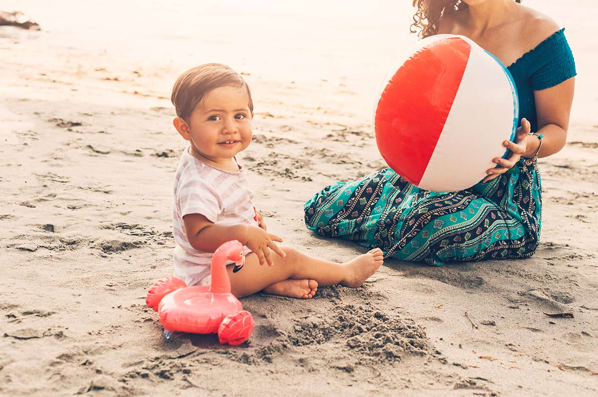 Baby boy sat in the sat on the Hawaiian beach next to an inflatable flamingo, his mum also sitting near him holding a beach ball.