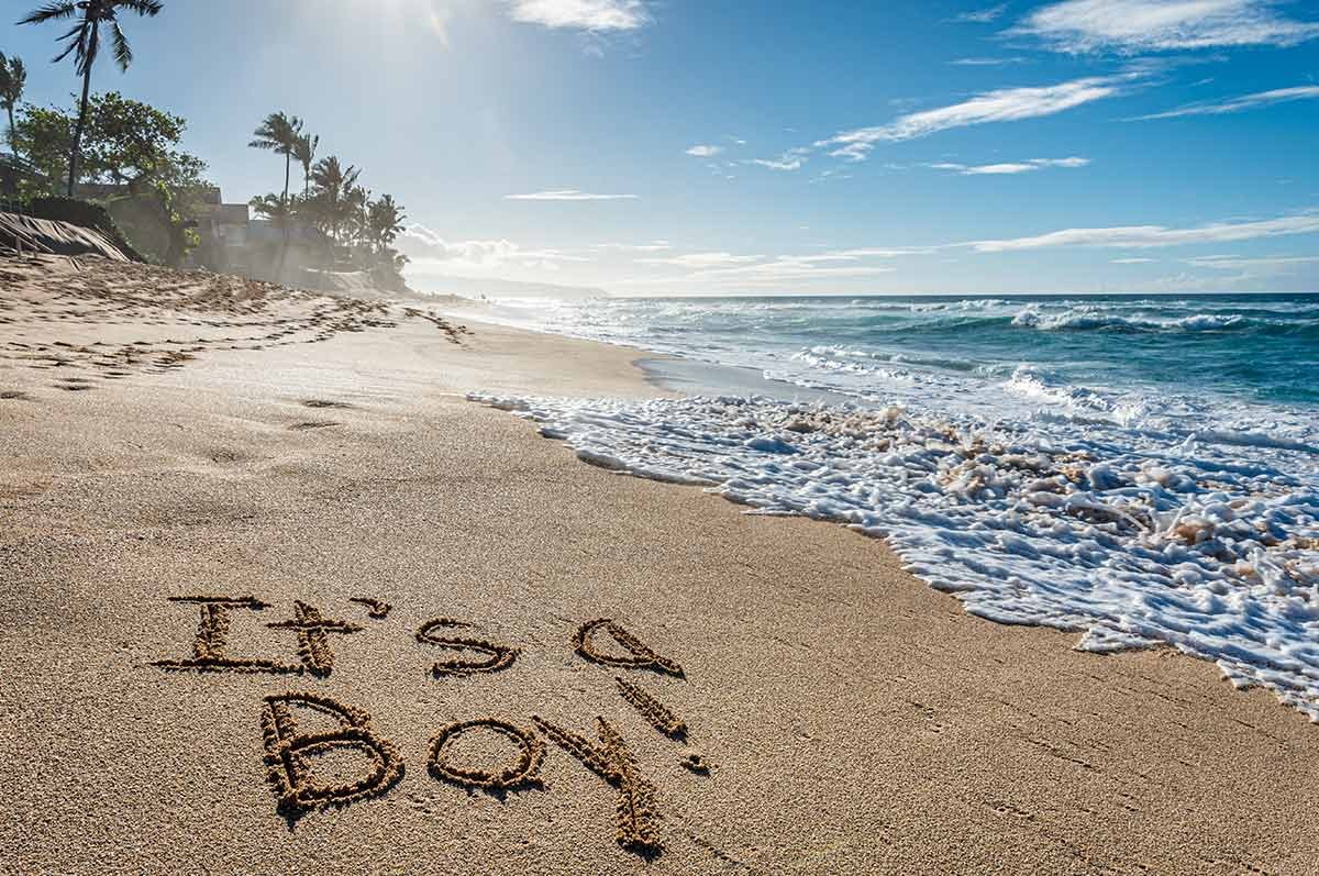 'It's a boy' written in the sand on the beach in Hawaii.