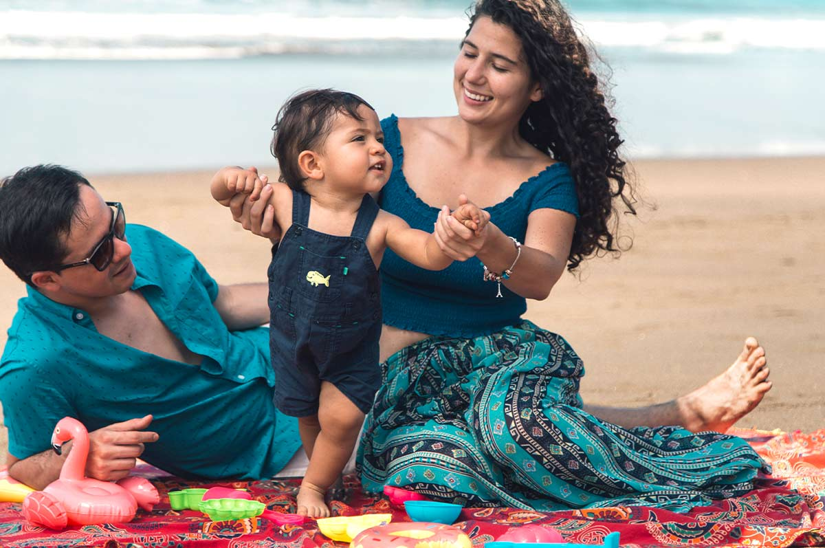 Parents sat on a rug in the sand on the Hawaiian beach playing with their baby boy.