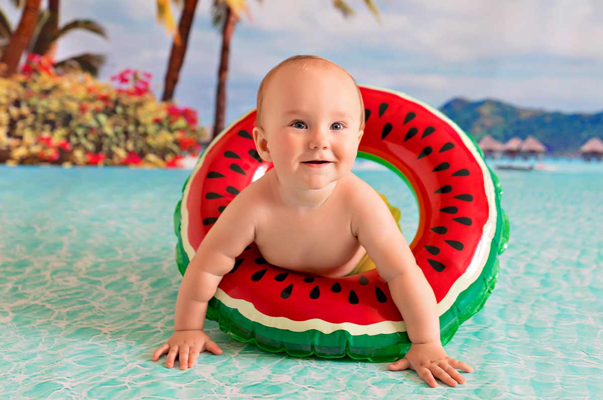 Baby boy wearing an inflatable watermelon ring crawling in the water.