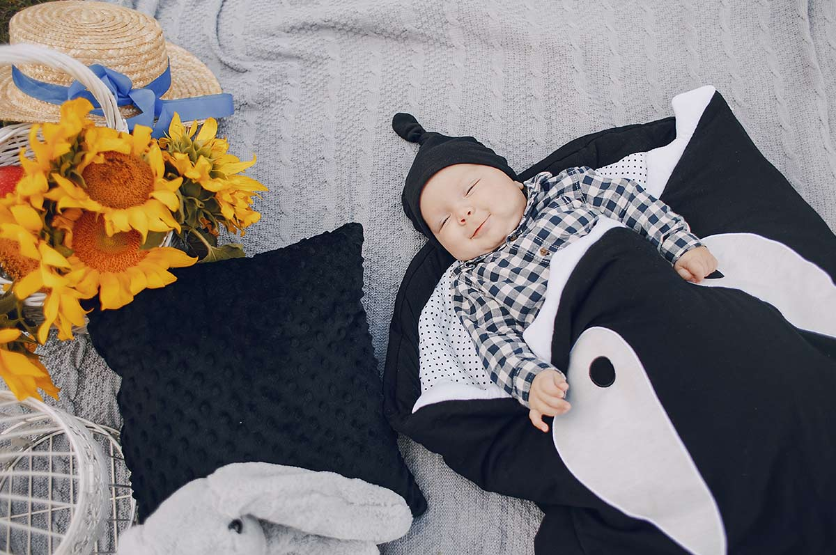 Baby boy lying on his back wrapped in an Orca whale blanket.