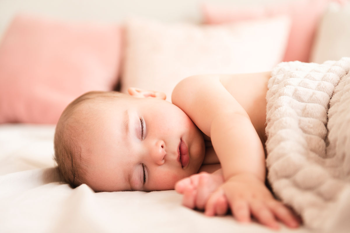 A baby lying on its side sleeping under a blanket.