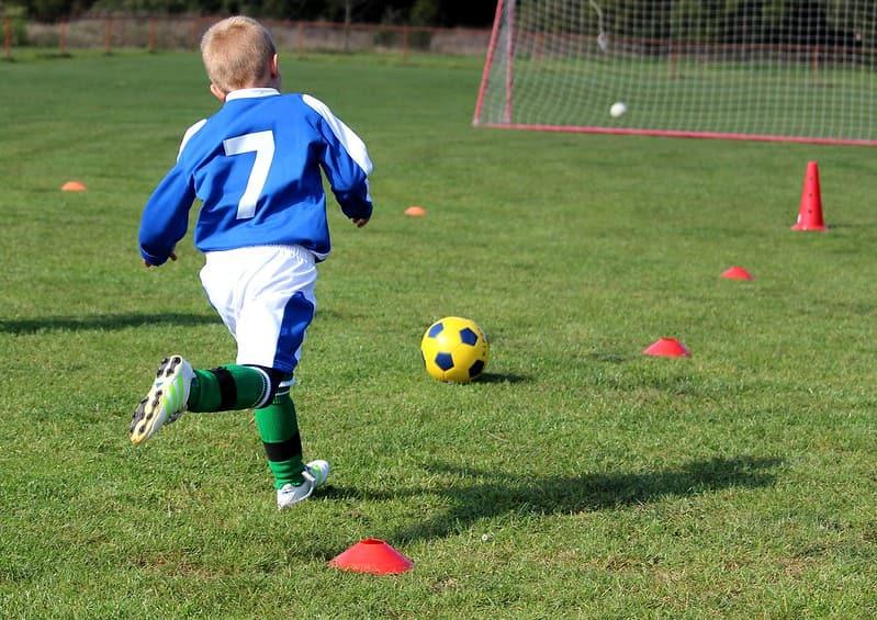 Young boy playing football wearing a blue jersey with number 7 on the back.