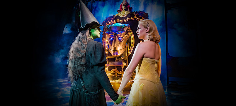 Glinda and Elphaba holding hands on the stage of Wicked The Musical with glowing blue light around them.