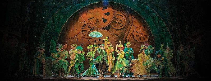 The cast of Wicked The Musical on stage dancing in wacky green costumes.