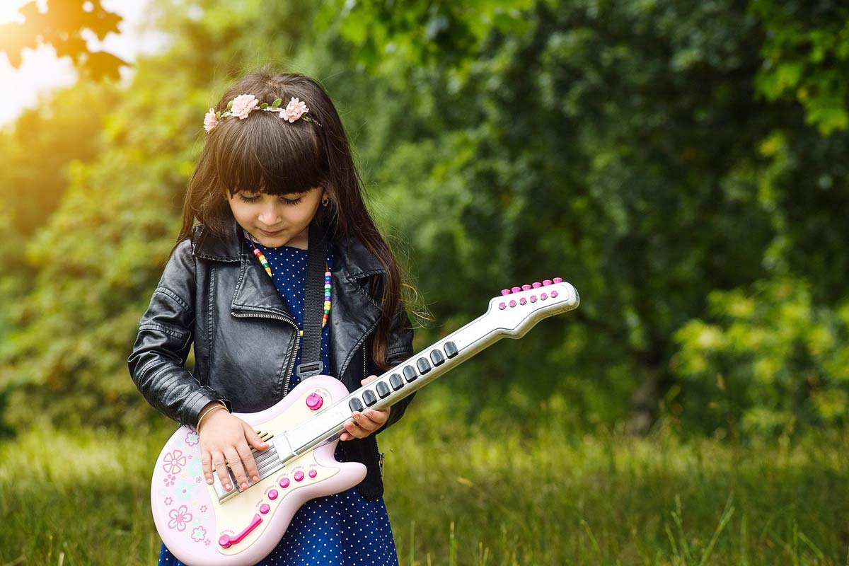 A little girls is outside playing a rock guitar.