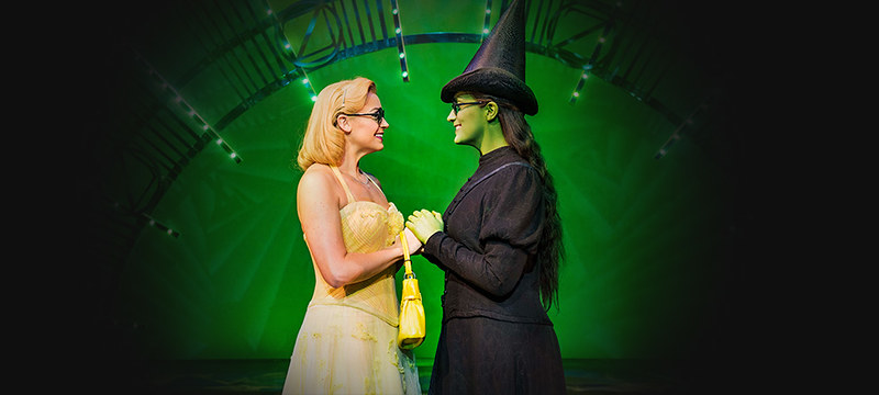 Glinda and Elphaba holding hands on stage at Wicked The Musical in front of green lights.