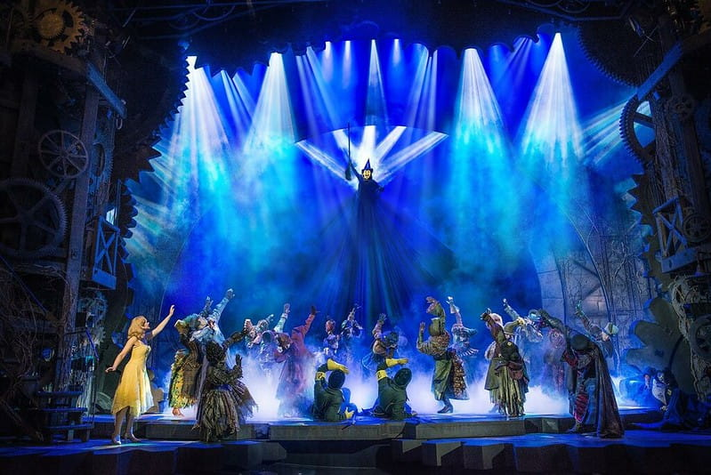 A dramatic scene from Wicked with Elphaba being lifted into the air as blue lights surround her.