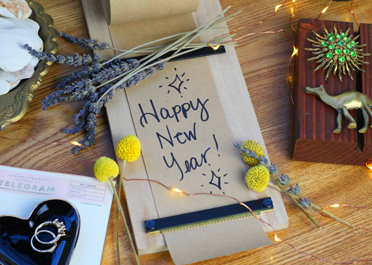 A Happy New Year card with flowers around it lying on the table.