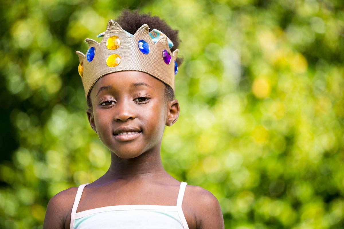 A young girl wearing a golden royal crown with blue and yellow jewels smiles at the camera.