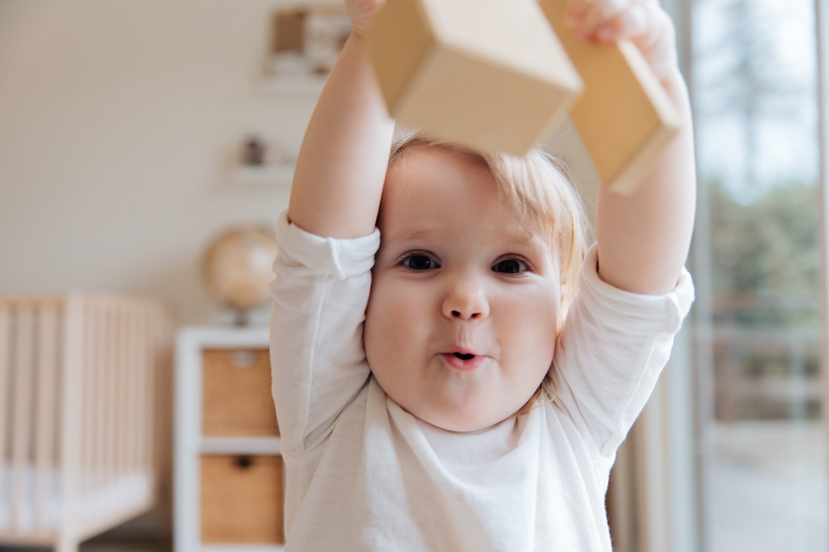 A baby pulls a funny face at the camera as they lift both arms above their head.