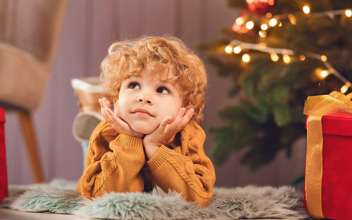 Little boy lying on his stomach by the base of the Christmas tree thinking about answers to Christmas riddles.
