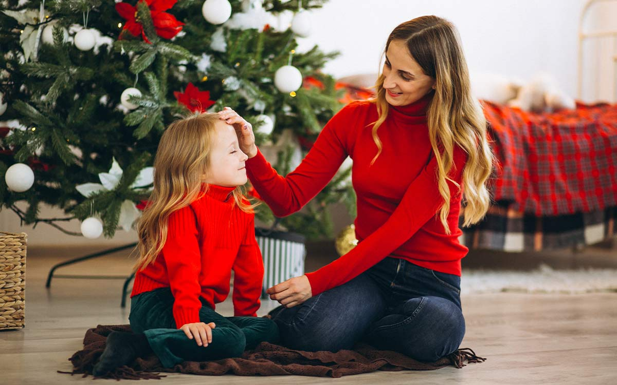Mum and daughter sat on the floor by the Christmas tree smiling as they discuss Christmas riddles.