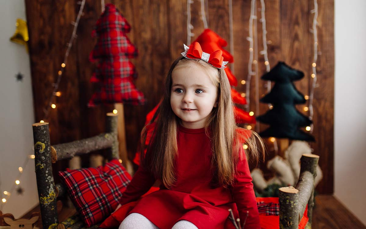 Little girl sat on a seat with Christmas decorations behind, thinking about the answers to Christmas riddles.