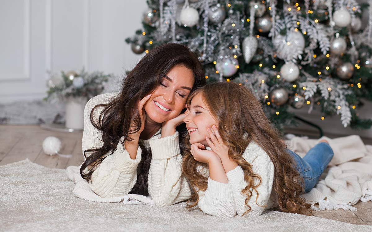 Mum and daughter lying on the ground by the Christmas tree smiling as they think about Christmas riddles.