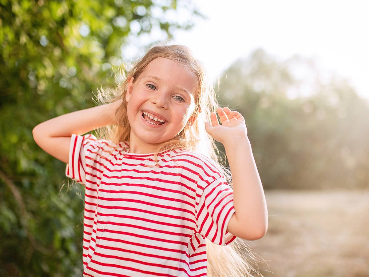 Girl wearing striped red and white top standing in the garden in the sun smiling at summer puns.