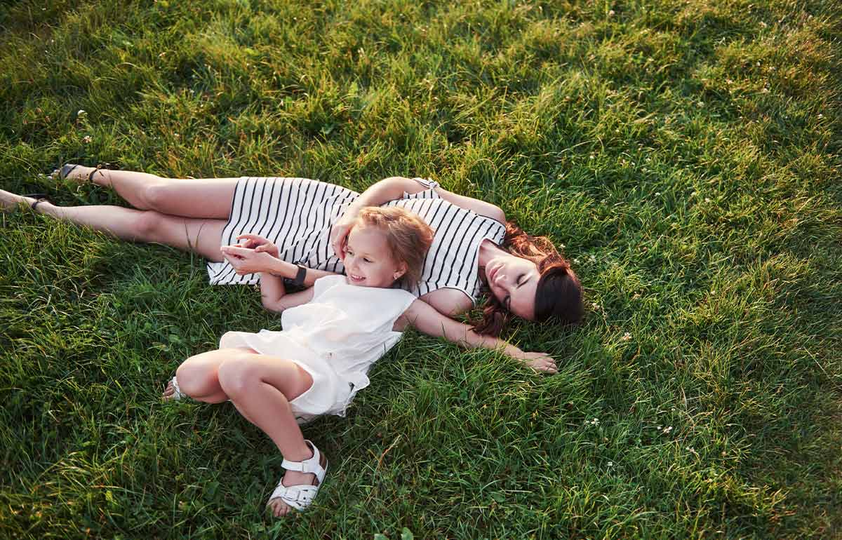 Mum and daughter lying in the grass smiling at summer puns.