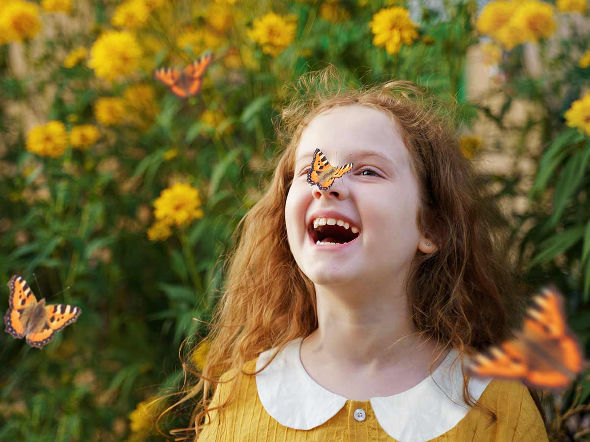 Girl standing by some plants in a garden with an orange butterfly on her nose, laughing at summer puns.