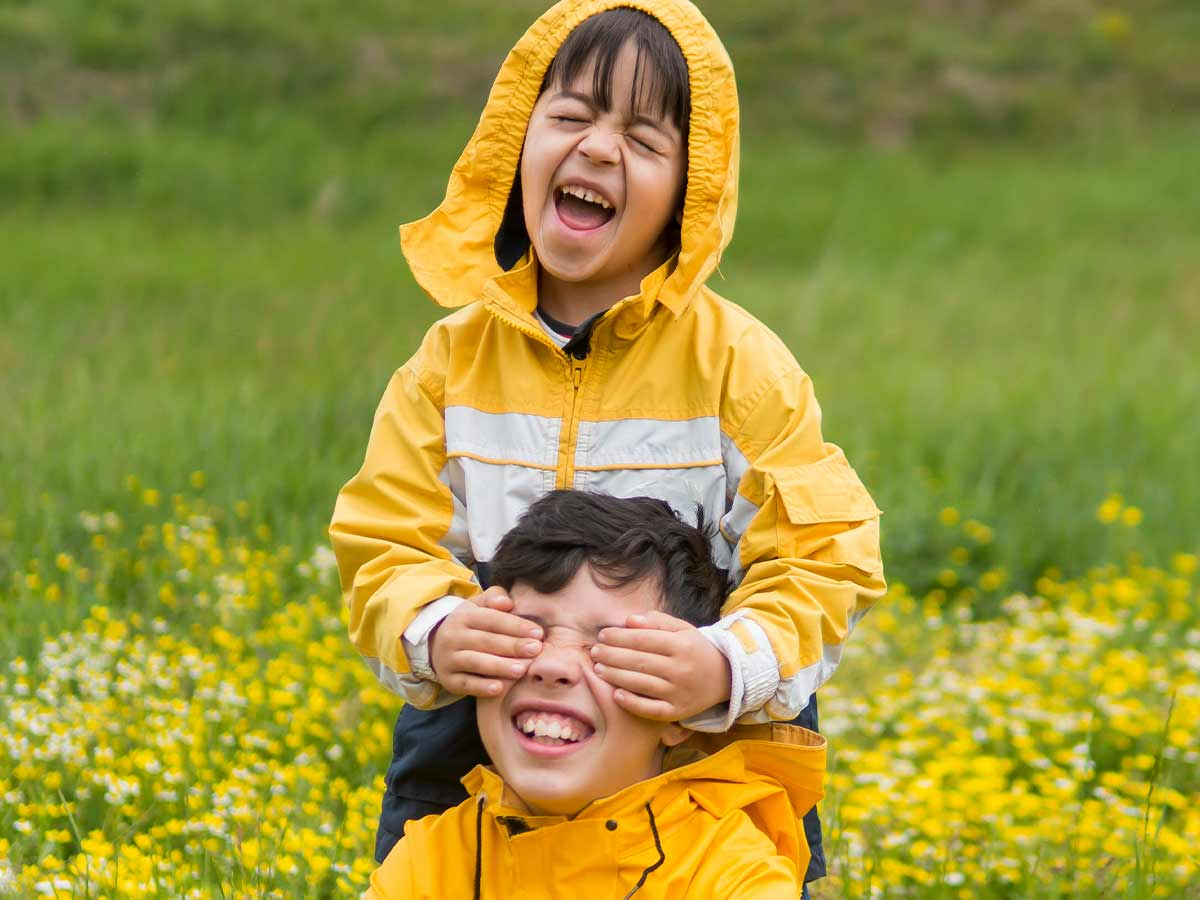 Two siblings wearing matching raincoats laughing in the garden together at summer puns.