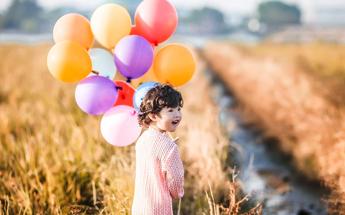 Young girl walking in a field holding  bunch of colourful balloons - an example of how gases work for KS2 kids.