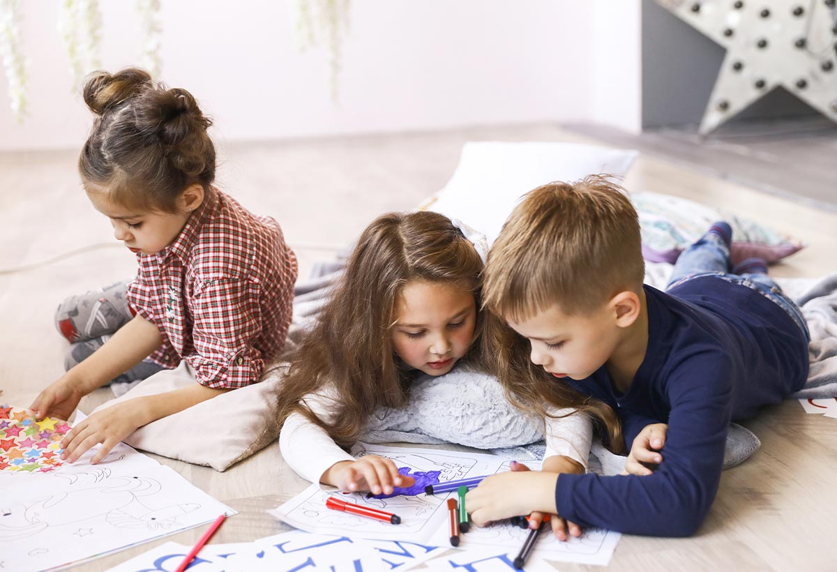 Three young kids lying on the floor drawing on paper to help learn about the passive voice.