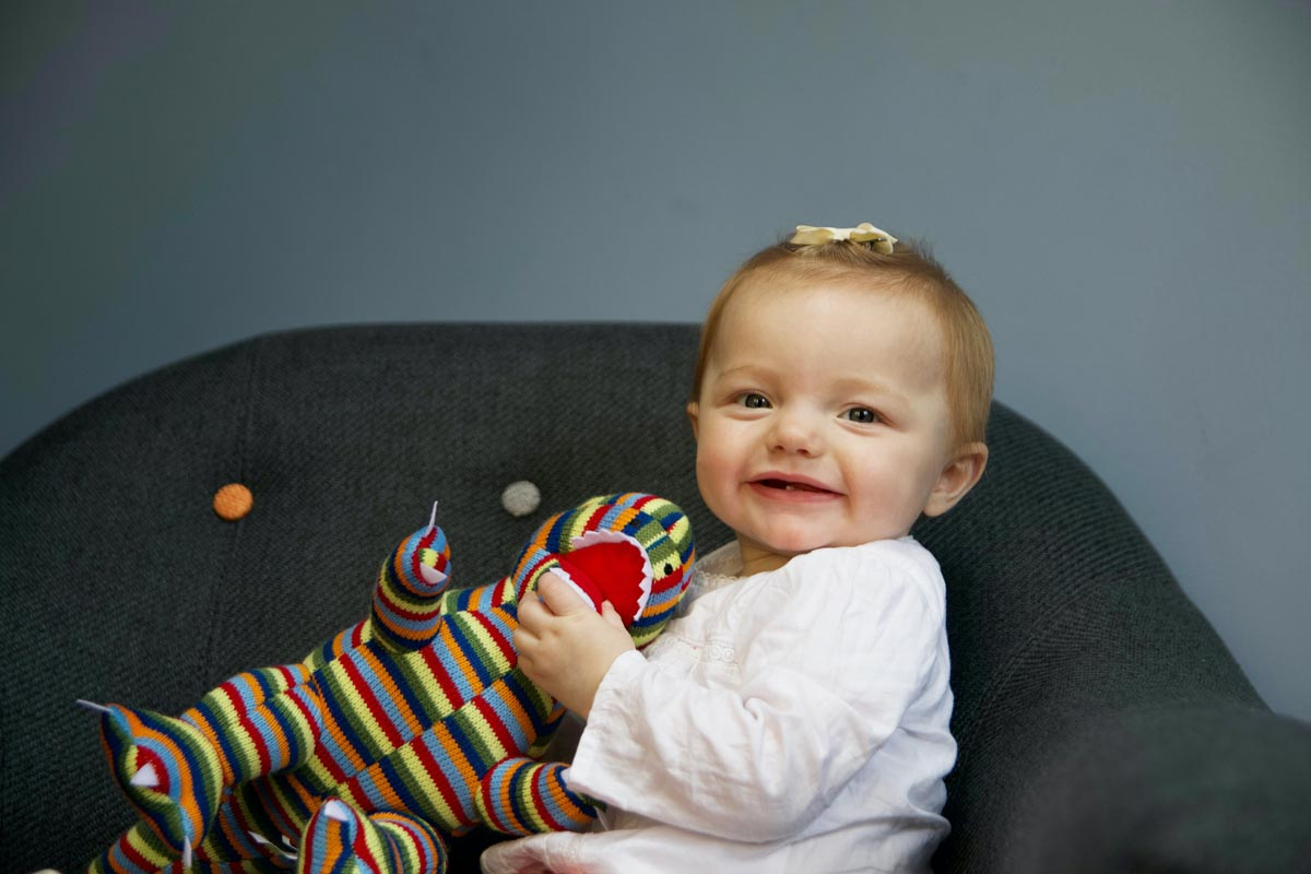 A baby girl is sitting on an armchair and smiling at the camera whilst holding a soft toy.